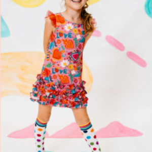 Girls pink dress by Rosalita Senoritas, with a colourful floral print. It has red tulle frills on the shoulders and ruffle details on the skirt. The dress fastens with a zip on the back.