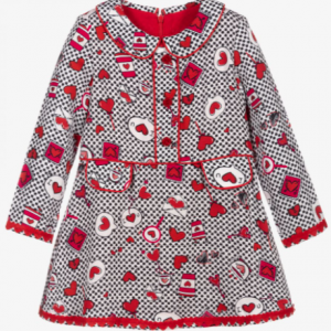 Girls dress by Rosalita Senoritas, with sweet black and red heart print on a white background. There is red piping details and felt heart trim on the sleeves and hemline. It has a rounded collar and decorative buttons and pocket flaps on the front. The dress is lined with cotton and has a back zip fastening.