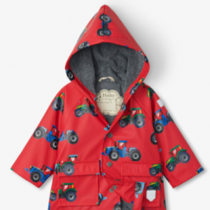 Red waterproof raincoat for baby boys by Hatley, with an attached hood. It has a silky smooth PVC-free outer shell, patterned in a blue, green and grey tractor print. Lined in soft grey towelling and with front popper fastenings, this fun raincoat has flap pockets and reflective logos.