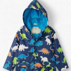 Navy blue waterproof raincoat for baby boys by Hatley, with an attached hood. The silky soft PVC-free outer shell is patterned in a green, blue and orange dinosaur print that changes colour when wet. Lined in bright blue towelling and with front popper fastenings, this fun raincoat has flap pockets and reflective logos.