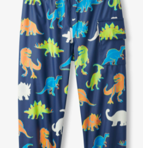 Boys blue rain trousers by Hatley, with a blue, green and orange 'Linework Dinos' pattern that changes colour when wet. The soft trousers are PVC free and have a velcro-fastening flap pocket. They have an elasticated drawstring waistband and elasticated leg cuffs.