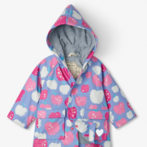 Purple waterproof raincoat for baby girls by Hatley, with an attached hood. It has a silky smooth PVC-free outer shell, patterned in a pink, white and blue apple print. Lined in soft grey towelling and with front popper fastenings, this fun raincoat has flap pockets and reflective logos.