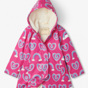 Pink waterproof raincoat for girls by Hatley, with a fully attached hood. With a super soft PVC free outer shell, it is patterned with blue, pink and purple rainbow hearts. It is lined with lightweight ivory sherpa fleece, fastens with purple poppers on the front and has a reflective logo on the sleeve.